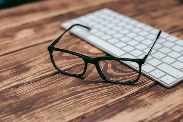 Bril voor zicht- en zichtcorrectie en bescherming tegen de computer op de houten tafel op het toetsenbord