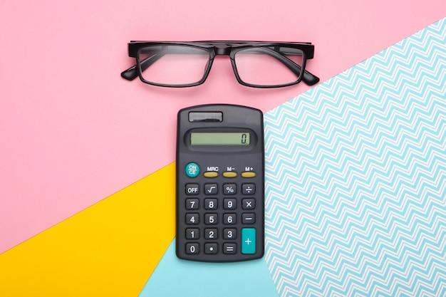 Brillen en rekenmachine op een pastelkleurige achtergrond. bovenaanzicht