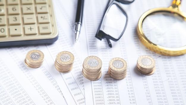 Brillen, munten, rekenmachine, pen op financiële documenten. bedrijf. financiën