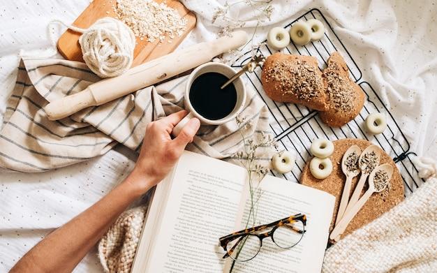 Brillen op de top van een boek rond voedsel en een hand met een kopje koffie