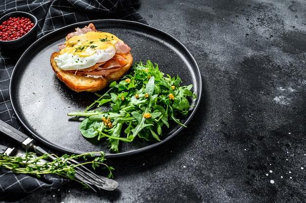Brioche sandwich met spek, egg benedict en hollandaise saus. garneer met rucola-salade. zwarte achtergrond. bovenaanzicht. kopieer ruimte