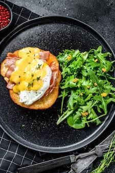 Brioche sandwich met spek, egg benedict en hollandaise saus. garneer met rucola-salade. zwarte achtergrond. bovenaanzicht