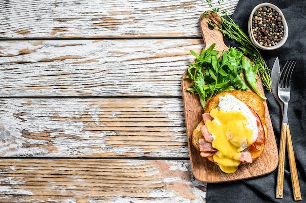 Brioche sandwich met spek, egg benedict en hollandaise saus. witte achtergrond. bovenaanzicht. kopieer ruimte