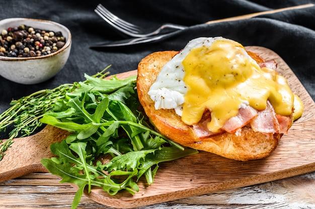Brioche sandwich met spek, egg benedict en hollandaise saus. witte achtergrond. bovenaanzicht