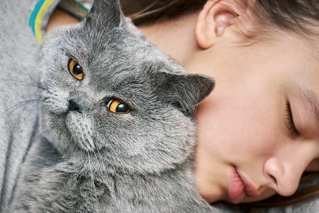 Brits korthaar kater liggend met een slapende tiener meisje en kijken naar de camera