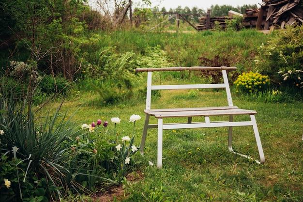 Britse achtertuin met een betegeld terras en traditionele houten bank.