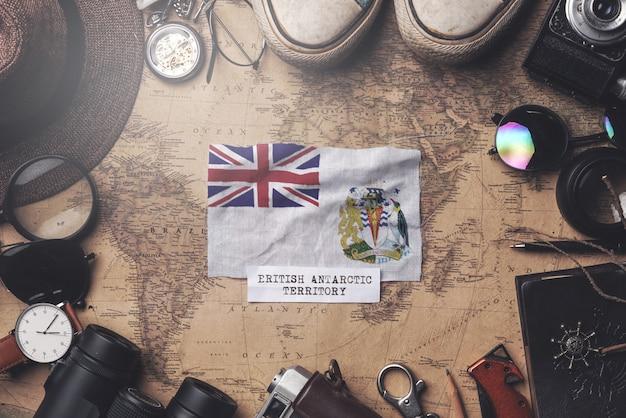 Britse antarctische territoriumvlag tussen de accessoires van de reiziger op oude vintage kaart. overhead schot