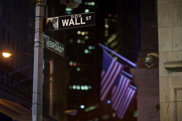 Broadway en wall street-borden in de nacht met amerikaanse vlaggen op het oppervlak, manhattan, new york