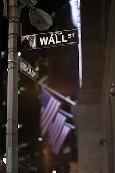 Broadway en wall street signs 's nachts met amerikaanse vlaggen op de achtergrond, manhattan, new york