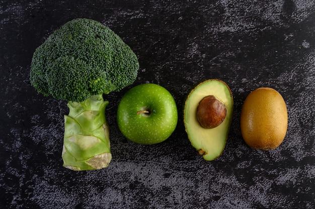 Broccoli, appel, avocado en kiwi op een zwarte cementvloer.