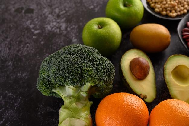 Broccoli, appel, sinaasappel, kiwi en avocado op een zwarte cementvloer.