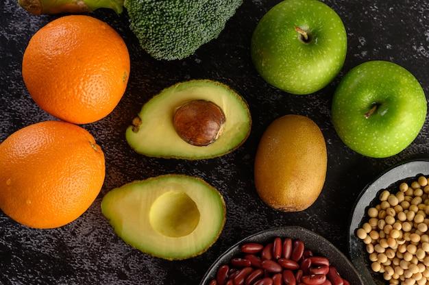 Broccoli, appel, sinaasappel, kiwi, peulvruchten en avocado op een zwarte cementvloer.