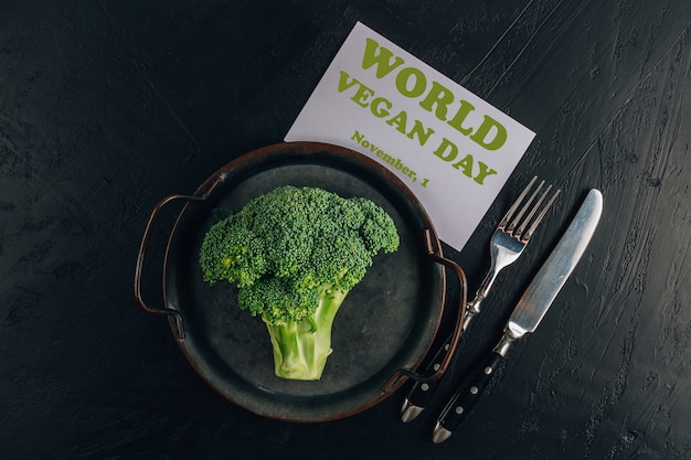 Broccoli en bestek op een zwarte achtergrond. de inscriptie