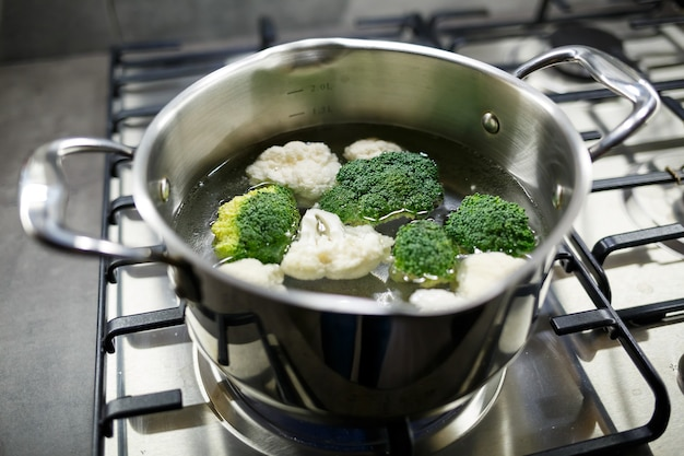 Broccoli en bloemkool gekookt in een grijze pan op een gasfornuis