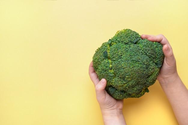 Broccoli in handen van kinderen op een gele achtergrond