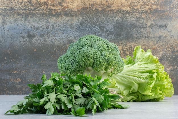 Broccoli, korianderblaadjes en sla op stenen oppervlak. hoge kwaliteit foto