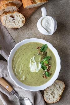 Broccoliroomsoep geserveerd met munt, room, zaden en brood. gezond vegetarisch voedselconcept.