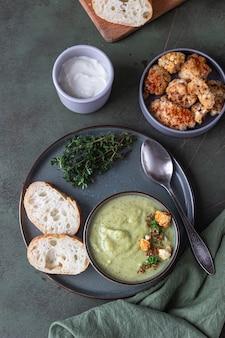 Broccoliroomsoep versierd met tijm, room, geroosterde bloemkool en vers brood.