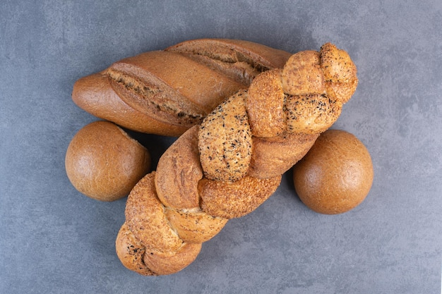 Broden van stokbrood, strucia en broodje brood gebundeld op marmeren achtergrond. hoge kwaliteit foto