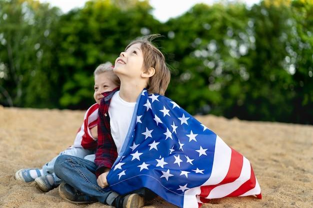 Broer en zus aan de kust, gehuld in een amerikaanse vlag, blije lachende kinderen, een meisje en een jongen, het concept van patriottisme en de viering van de amerikaanse onafhankelijkheid. amerikaanse veteranendag.