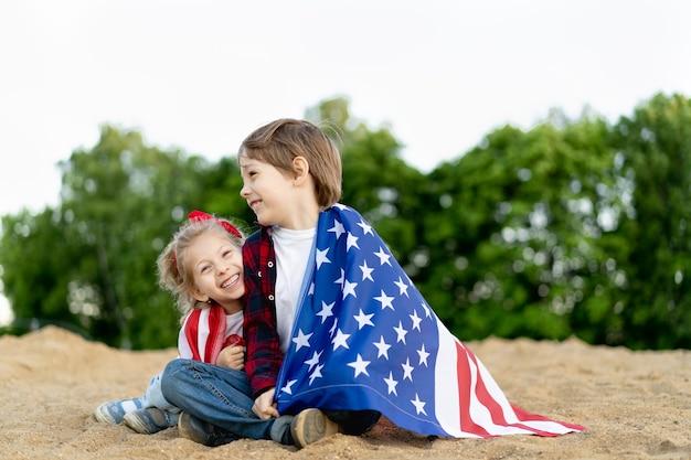 Broer en zus aan de kust, gewikkeld in de amerikaanse vlag, gelukkige kinderen lachen, meisje en jongen concept van patriottisme en de viering van de amerikaanse onafhankelijkheid. amerikaanse veteranendag.