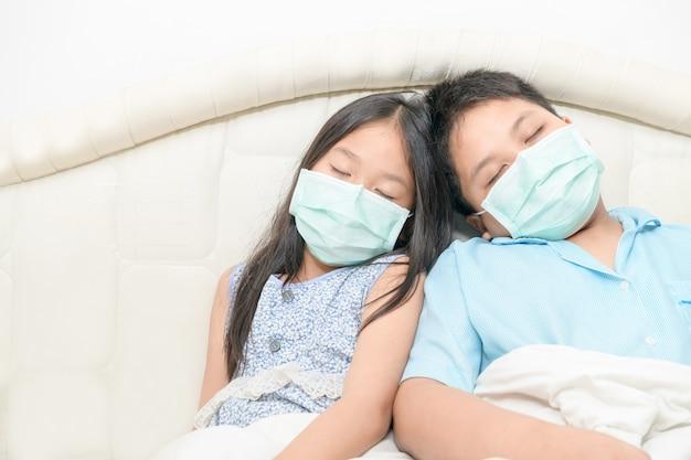 Broer en zus dragen chirurgische maskerslaap op bed, ziek kind