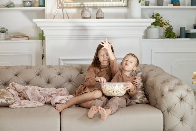 Broer en zus eten popcorn om thuis op de bank te zitten