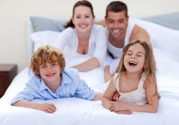 Broer en zus hebben plezier in bed met hun ouders