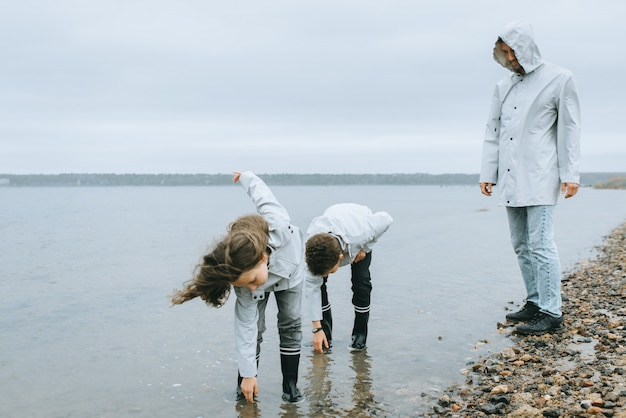 Broer en zus hebben plezier in de zee dragen in regenjas