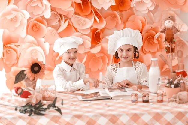 Broer en zus in een chef-kokuniform staan bij de keukentafel