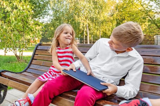 Broer en zus in het park op een bank halen een laptop van elkaar