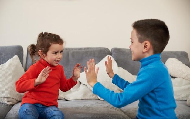 Broer en zus klappen in hun handen zittend op de bank. kinderen spelen samen.