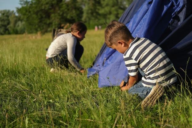 Broer en zus leren een tent op te zetten in het zomerveld buiten. familie wandeling. gelukkig gezin. hoge kwaliteit foto