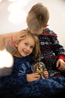 Broer en zus lezen boek in pyjama blote voeten avond slaap familie sleep