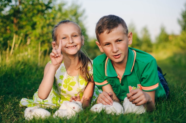 Broer en zus liggend op het gras met kleine konijnen. paashaas