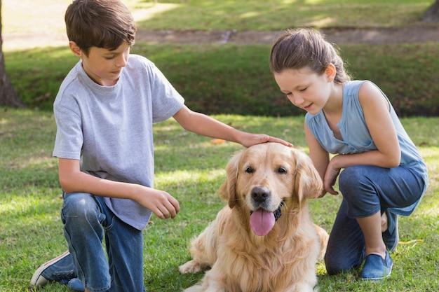 Broer en zus met hun hond in het park