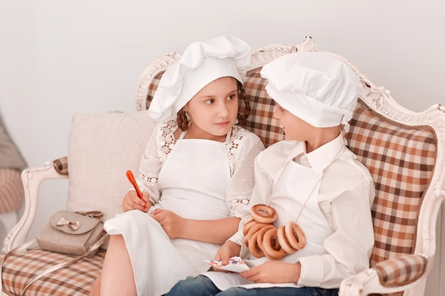 Broer en zus met koksmuts bespreken het lunchmenu.hobby's en interesses