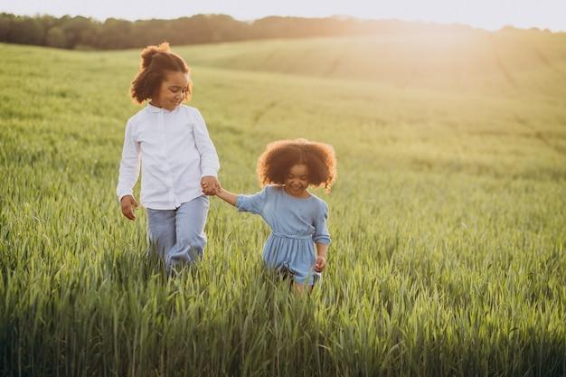 Broer en zus samen op het veld bij zonsondergang