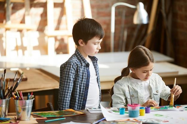 Broer en zus samen schilderen