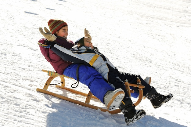 Broer en zus sleeën de heuvel af, sneeuw, winter, geluk en saamhorigheid