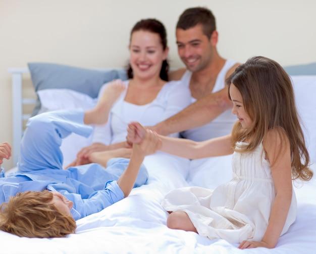 Broer en zus spelen in bed met hun ouders