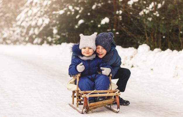 Broer en zus spelen in de winter op straat. kinderspellen in de natuur