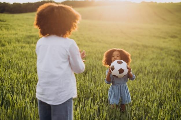 Broer en zus spelen met de bal op het veld