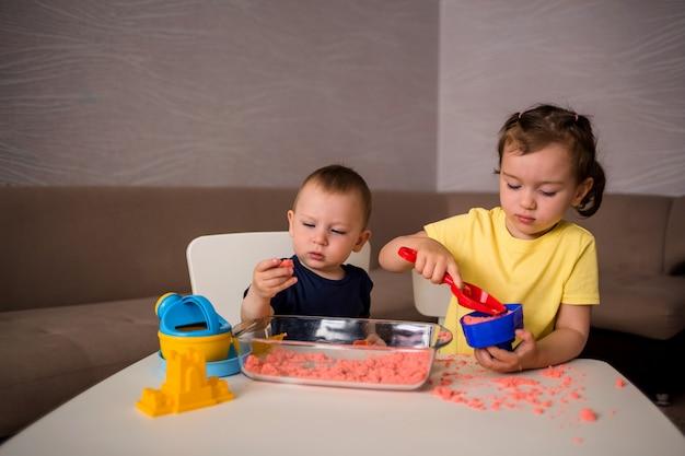 Broer en zus spelen met kinetisch zand aan de tafel in de kamer. sensorische ontwikkelingsgames voor kinderen thuis.