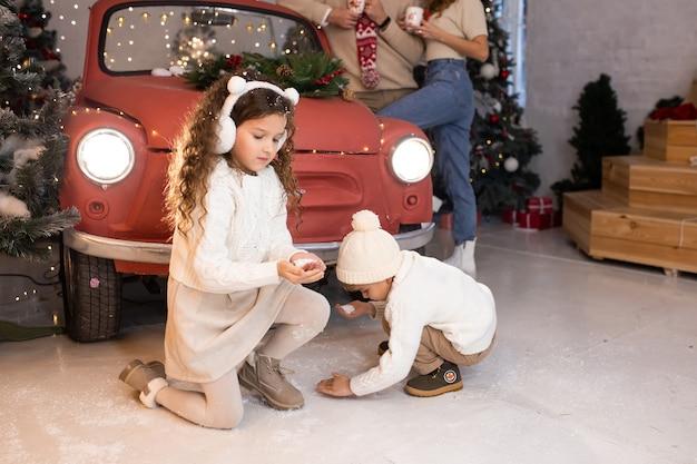 Broer en zus spelen met sneeuw in de buurt van kerstboom en verlichting