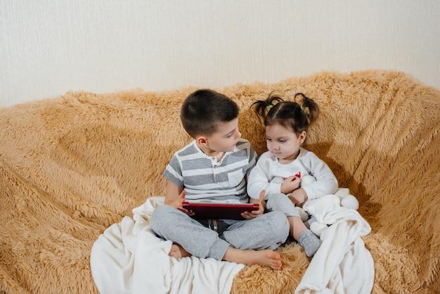 Broer en zus spelen op de bank in de tablet