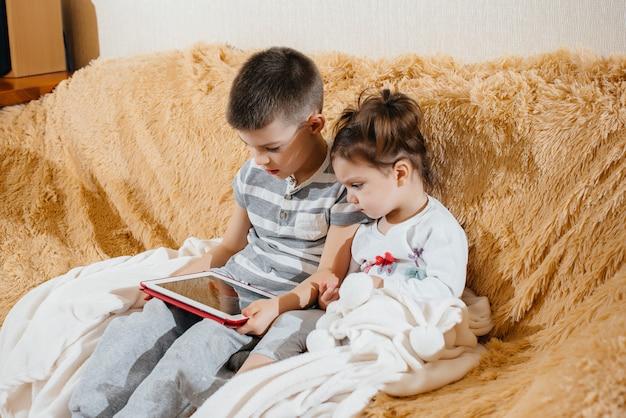 Broer en zus spelen op de bank in de tablet.