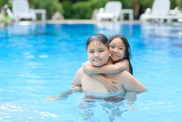 Broer en zus spelen water in het zwembad