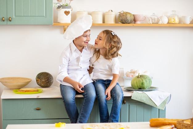 Broer en zus thuis in de keuken