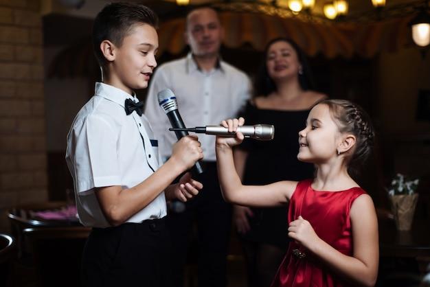 Broer en zus zingen karaoke-liedjes in microfoons en hun ouders zingen op de achtergrond